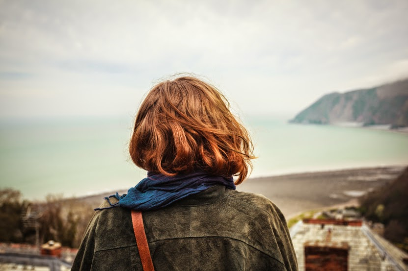 Young woman is admiring the seaside view from a hill